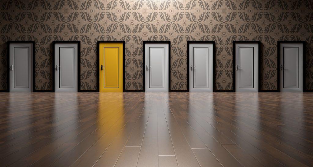 7 portes blanches alignées, dont 1 jaune