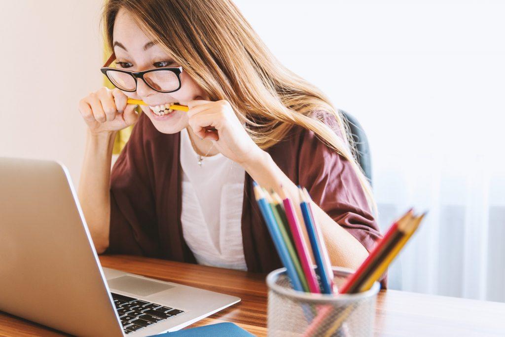 Jeune femme qui mord un crayon en regardant son ordinateur portable